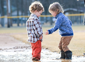 Two young boys are walking together in a muddy country field. One kid is helping the other child out