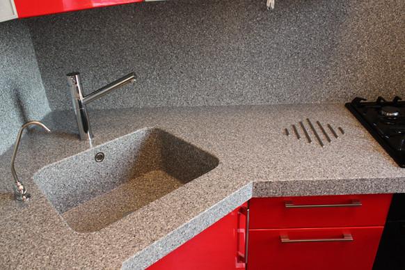 Столешница с мойкой из искусственного камня в кухне угловая