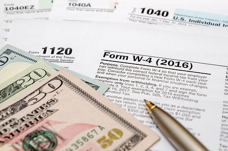 tax form w4, 1040, 1120 with pen and us