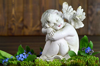 Angel and spring flowers on wooden backg