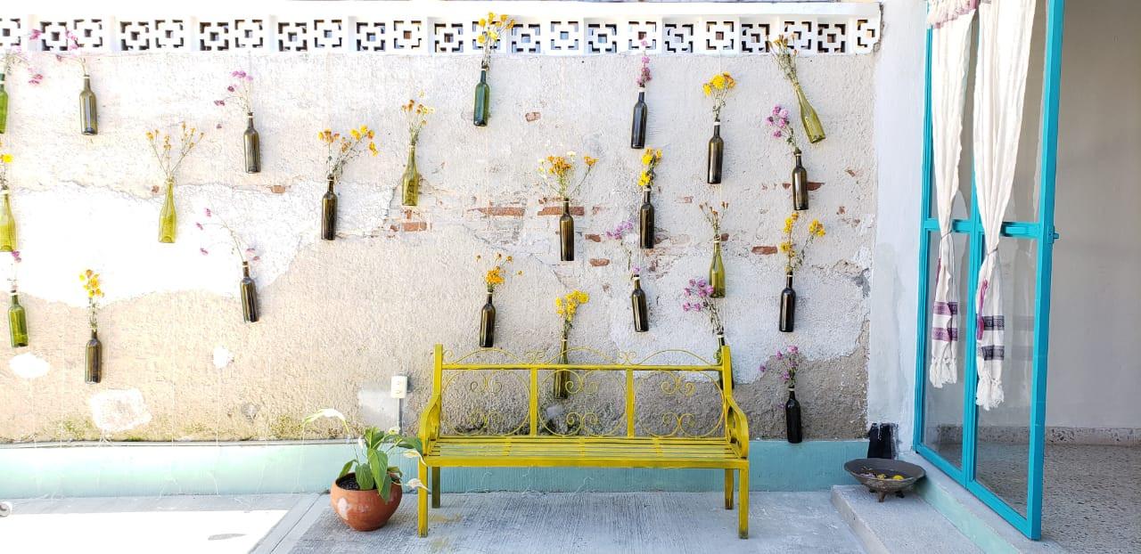 La pared de botellas y el banquito amarillo.