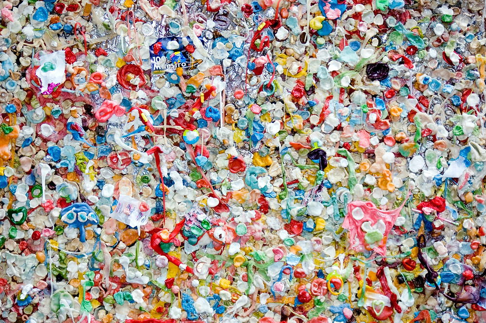 Abstract art piece made of used coloured chewing gums and waste.