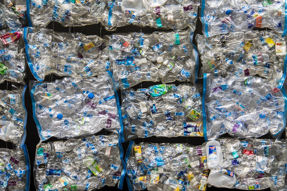 Plastic waste compacted together into bales. Each bale piled onto one another.