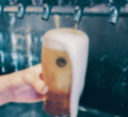 A closeup of a draft beer being poured and overflowing an ABC Pubs branded pint glass