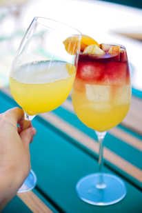 A hand toasts two orange weekend cocktails