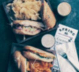 An overhead shot of the Hot Italiana sandwich and Pressman vegan sandwich, with two glases of beer and a menu.