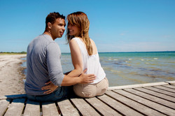 couple-sitting-on-a-pier-on-a-beautiful-sunny-day-at-the-beach_rTh40H4Yl