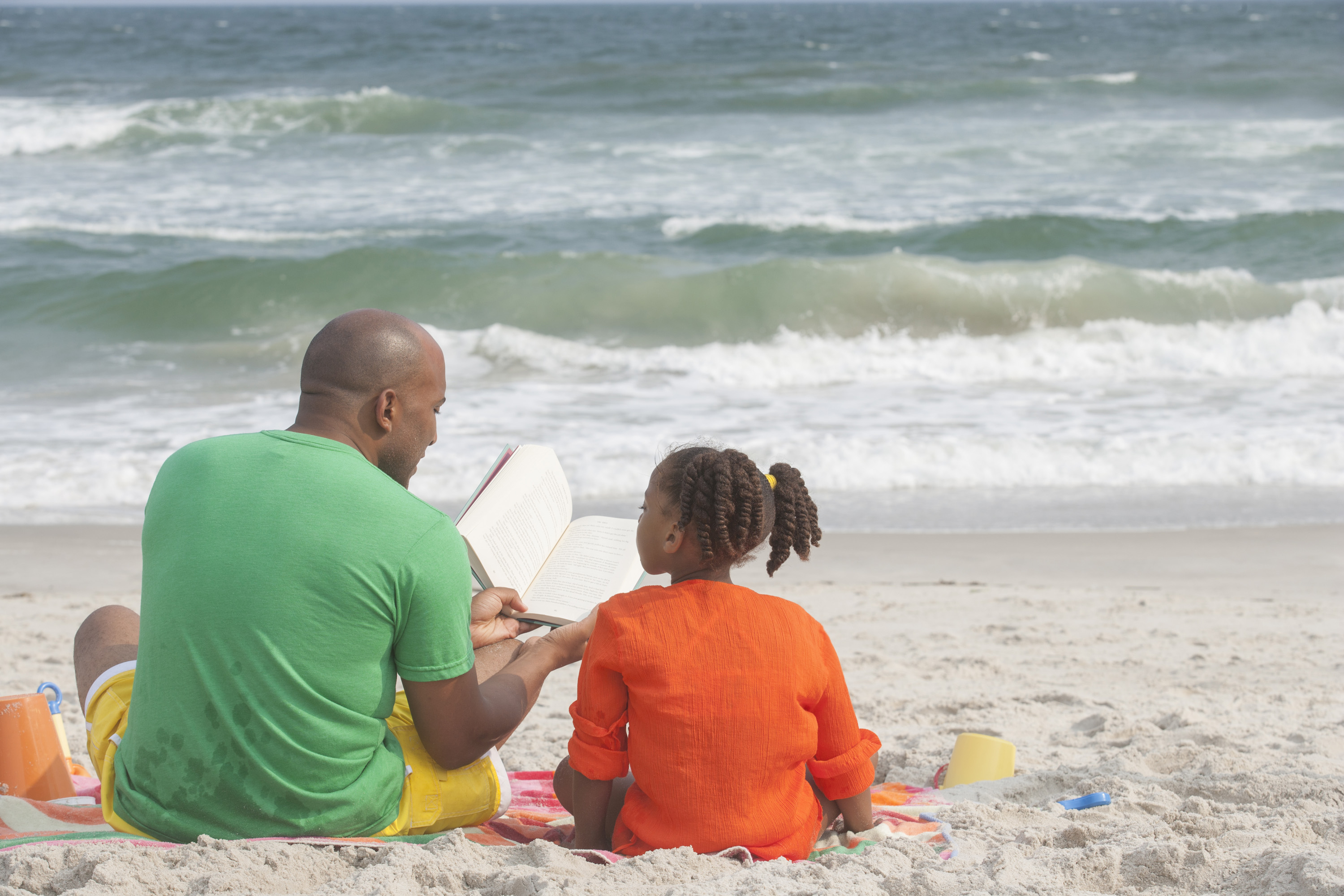 family-reading-at-the-beach_Stv53LRSo