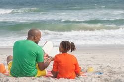 family-reading-at-the-beach_Stv53LRSo