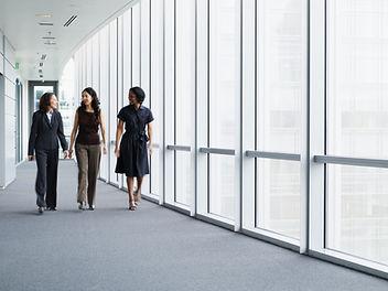 Деловые женщины гуляют в коридоре