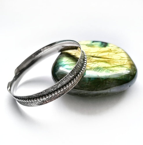 Beautiful silver convex floral patterned bangle with beaded spinner detail