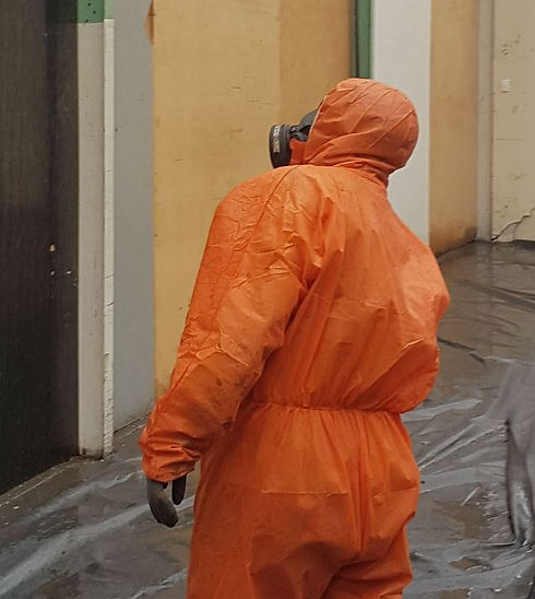 Man wearing protective body suit for asbestos removal.