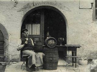Historischer Eingang mit Mann, Fass und Wein