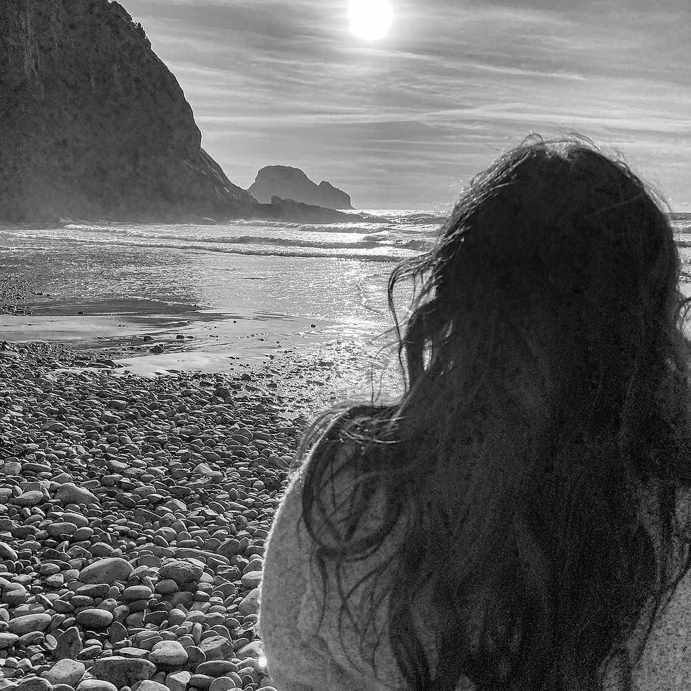 Black and white portrait of woman on the rocky beach in Oregon.