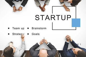 An image with start-up on a table with business people representing our start-up business coaching.