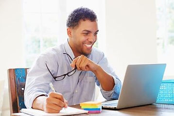 A man sitting at his computer talking to someone online representing our general business coaching.