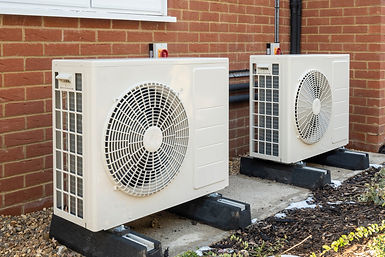 Two air source heat pumps installed on the exterior of a modern house.jpg