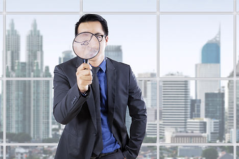 Young businessman looking through a magn