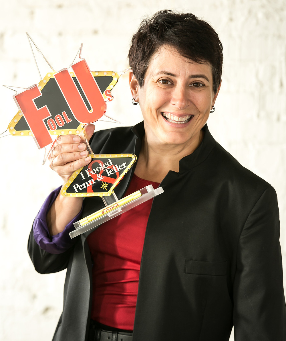 """Suzanne The Magician holding her """"Fooled U"""" Penn & Teller Award"""
