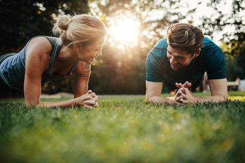 Fit young man and woman exercising in pa