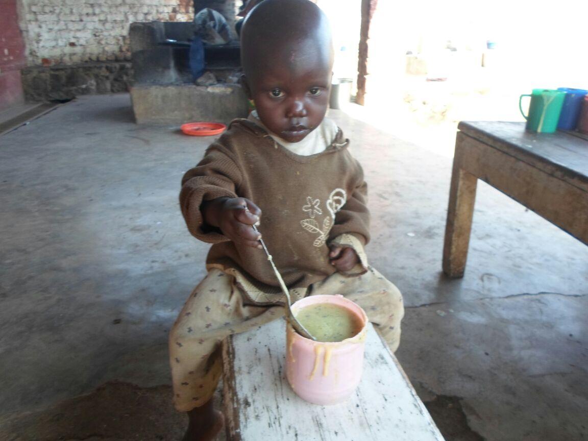child eating porridge in congo