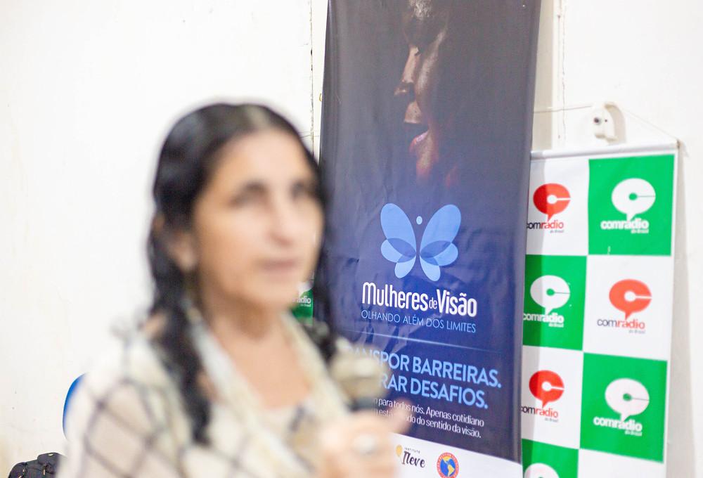 Participante do projeto Solange, ao fundo banner Mulheres de Visão e da Escola Comradio