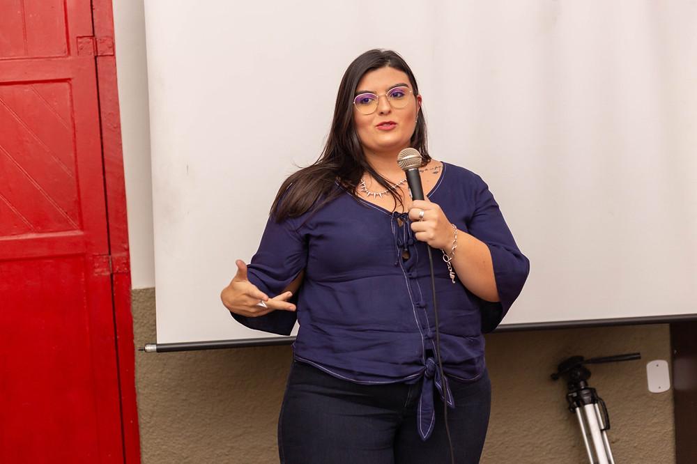 Produtora de Conteúdo Débora Nascimento falando ao microfone