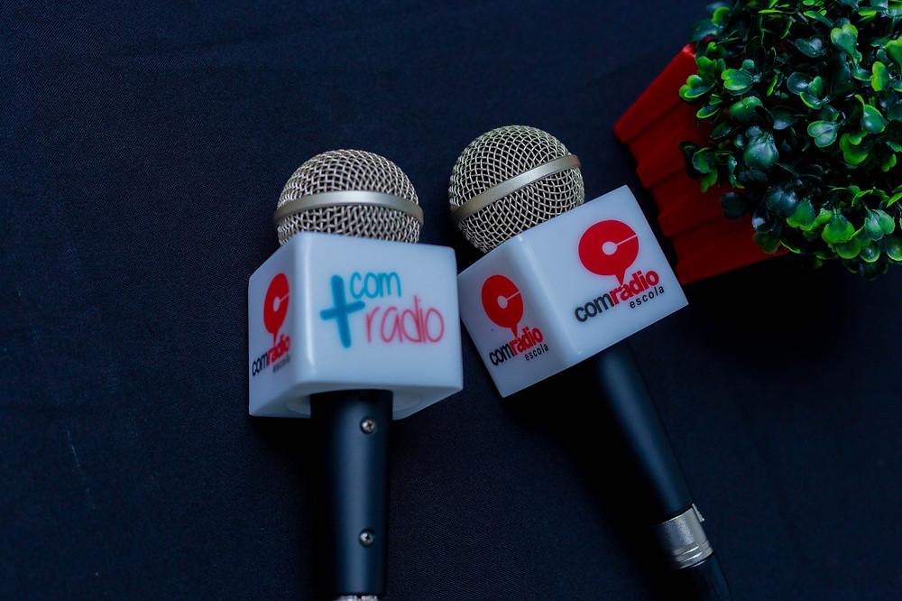 Dois Microfones com a canopla da Escola Comradio e Mais Comradio