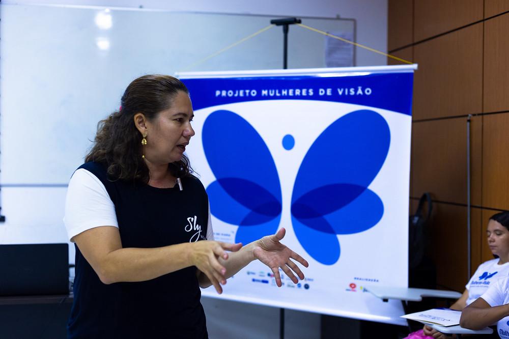 Professora Iolanda Bezerra falando e atrás um banner com uma borboleta, símbolo do Projeto Mulheres de Visão