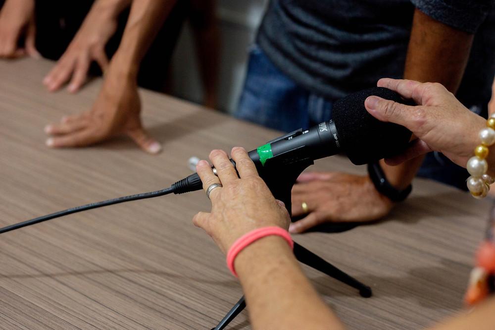 Mão de uma das participantes pegando em um microfone