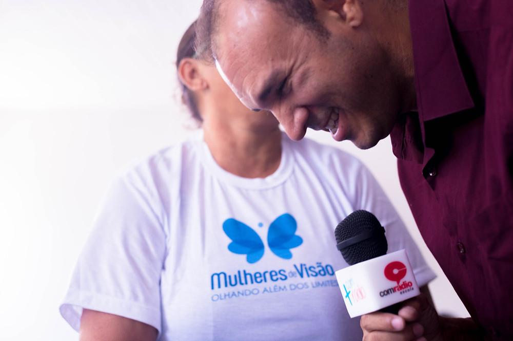 Professor Iraildon Mota, segurando um microfone e atrás uma das participantes do projeto com a camisa Mulheres de Visão.