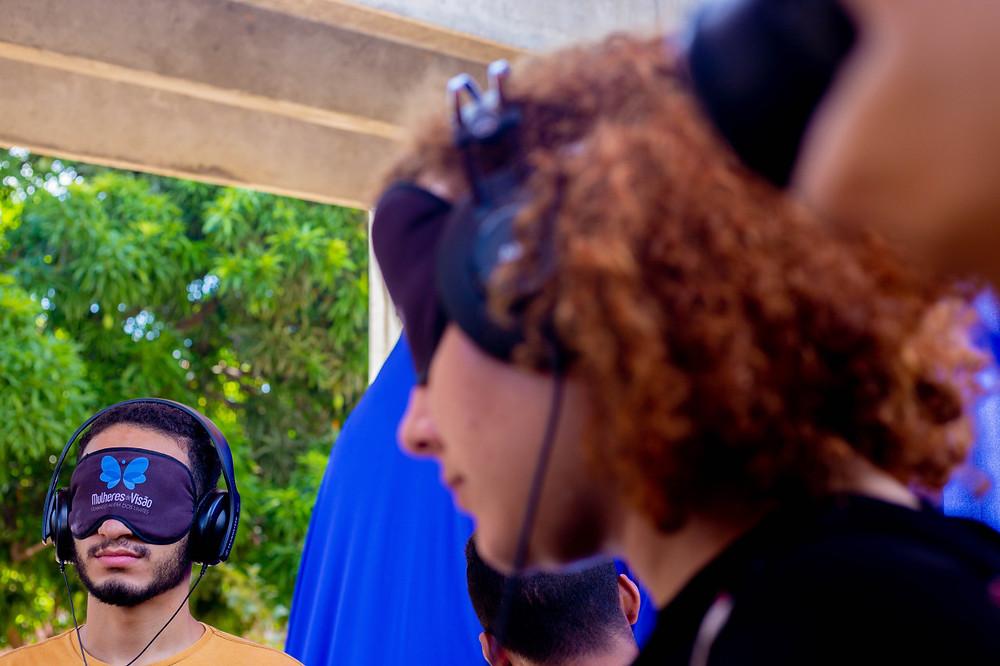 Dois alunos vendados com a marca do Projeto Mulheres de Visão, usando fone de ouvido.