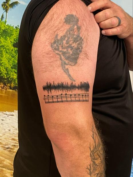 Drum line arm tattoo