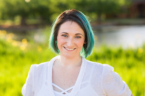 Smiling portrait, by Wildauer Photography, of Lizzie Stoxen with blue and green hair