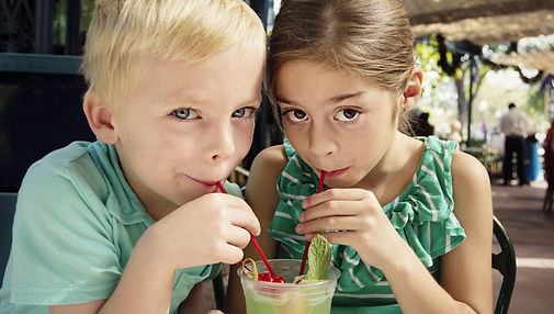 Cute kids sharing a mint julep drink at