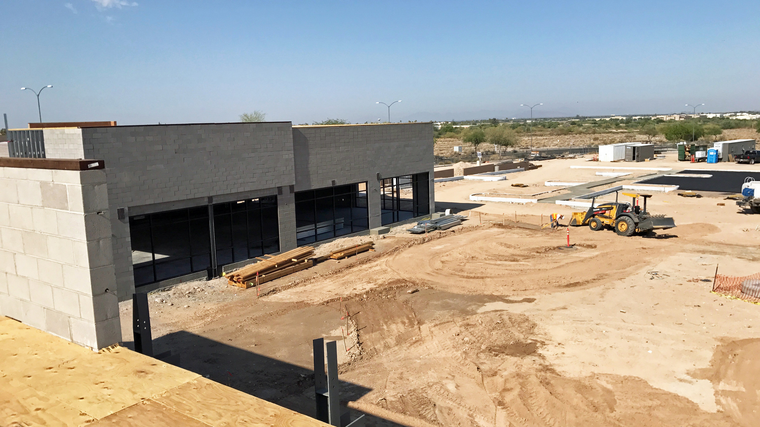 Shell of future restaurant and retail and Deere tractor cutting curb grade.