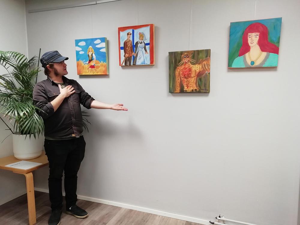 Kuvassa Sam Laurila ja näyttelyssä olevat teokset