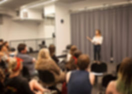 an acting studio class with a young teacher wearing white standing instructing the students sitting and listening