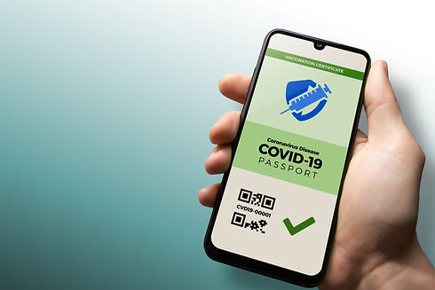 Vaccination passport for COVID-19 displayed on smartphone held in male's hand with copy sp