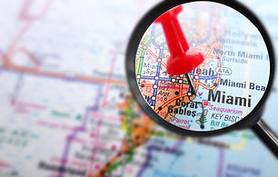 Closeup of Miami map with red push pin and magnifying glass                            .jp