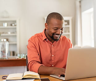Smiling black man using laptop at home i