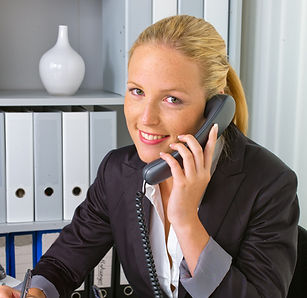 a friendly woman phoned at her desk in t
