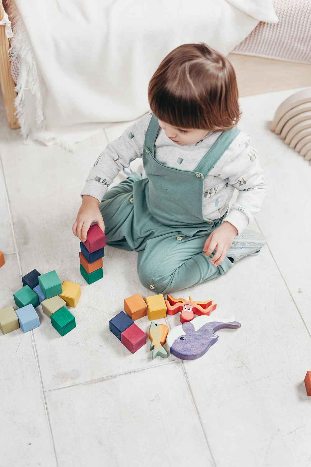 A toddler wearing grey and white coloured jumpsuit playing with her toys