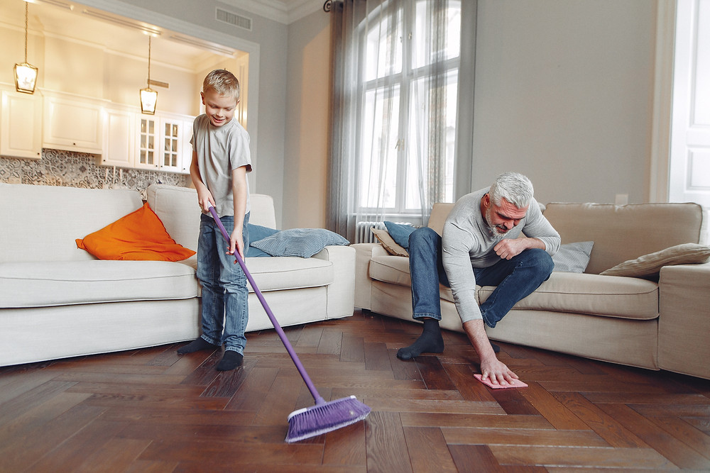 Man cleaning a floor with his child