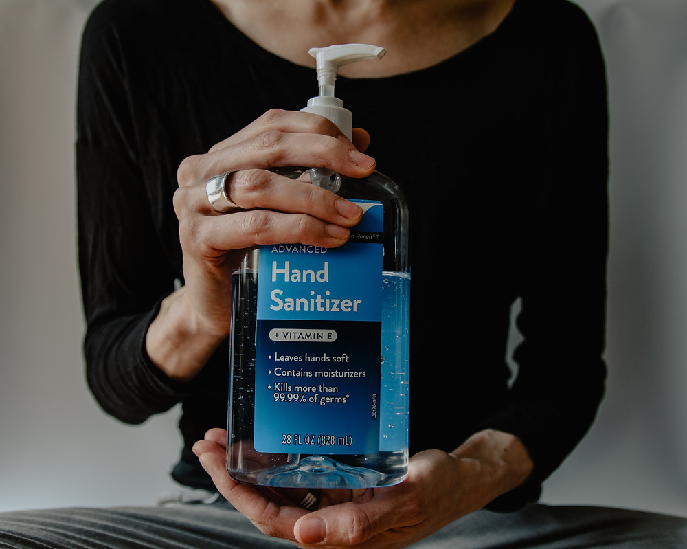 A lady holding a pump dispenser bottle of hand sanitizer