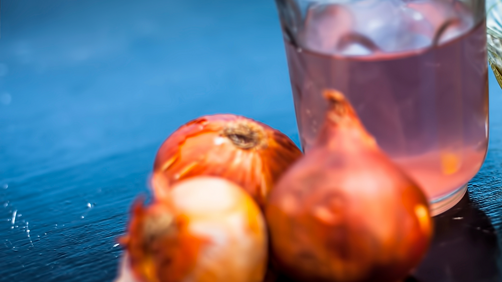 Three onions with their extracted juice in a glass