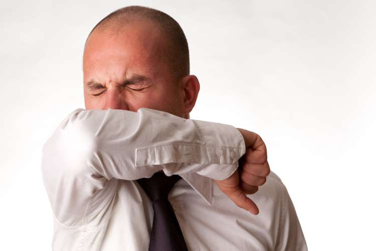 Man sneezing by covering up his mouth and nose with his flexed elbow