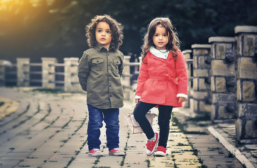 two kids standing in pose wearing jacket and jeans