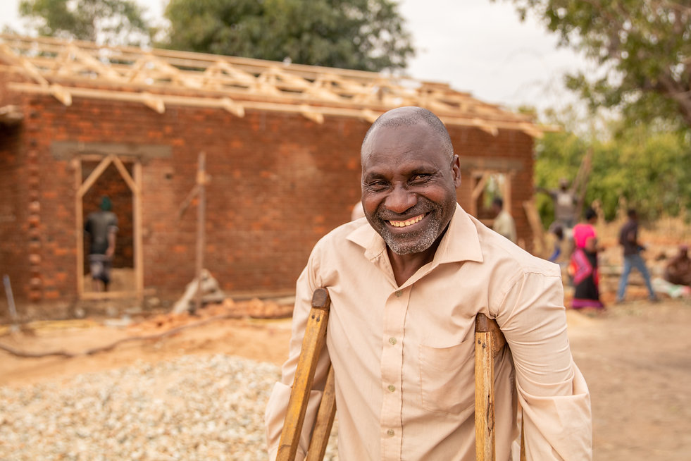 disabled man holding crutches smiles in front of the house being built for him in tanzania, africa