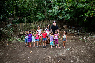 missionary stands with children in a dirt field in the philippines
